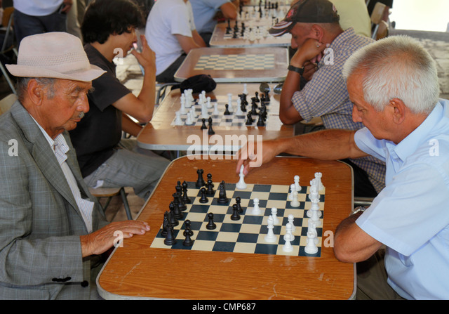 Chile Santiago Plaza de Armas main public square park Hispanic man men chess board game chessboard strategy player - Stock Image