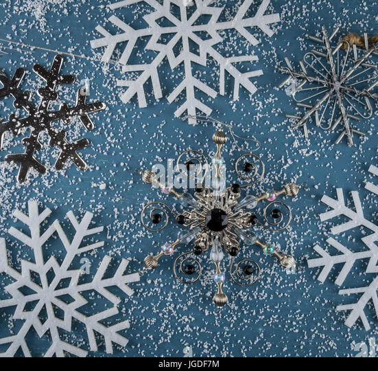 Snowflake Ornaments and snow scattered across blue background Square - Stock Image