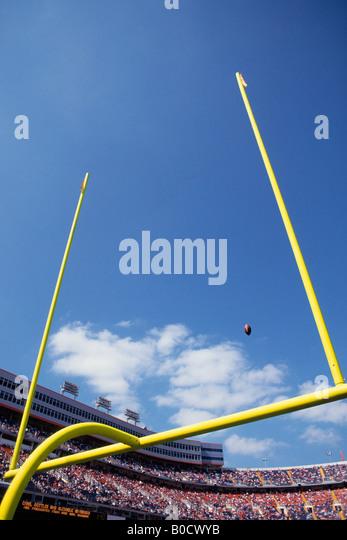 American football flying through the goalposts. - Stock Image
