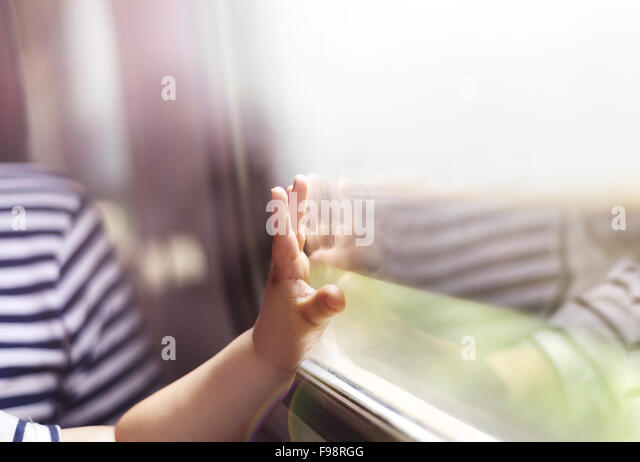 Boy travelling in retro train. He is touching the window. - Stock Image
