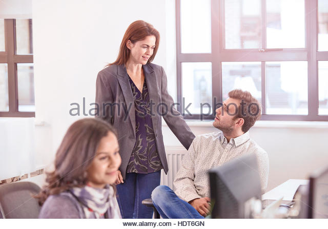 Co-workers discussing work in office. - Stock Image
