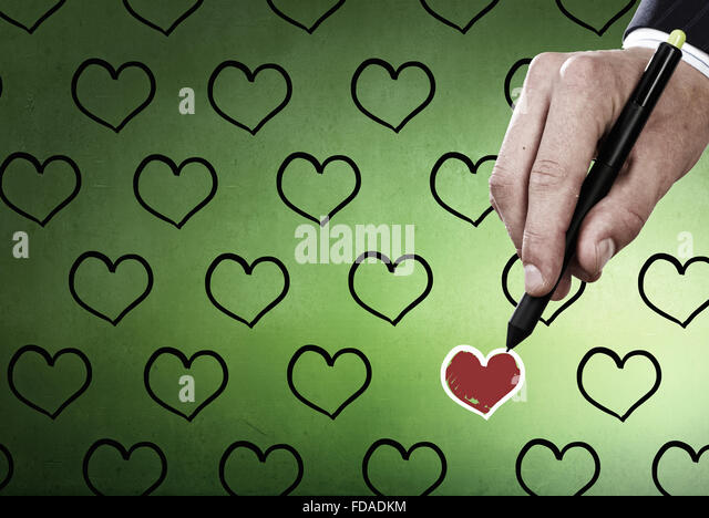 Male hand drawing red heart with marker - Stock Image