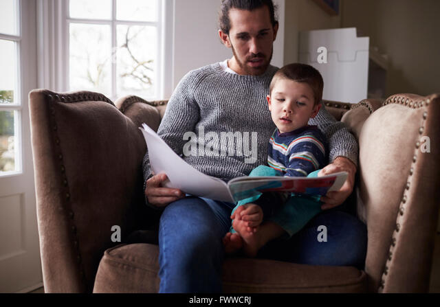 Father Sitting In Chair At Home Reading Story To Son - Stock Image