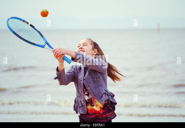 Young girl (12-13) playing tennis - Stock Image