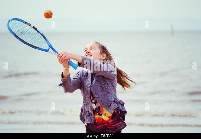 Young girl (12-13) playing tennis - Stock Image