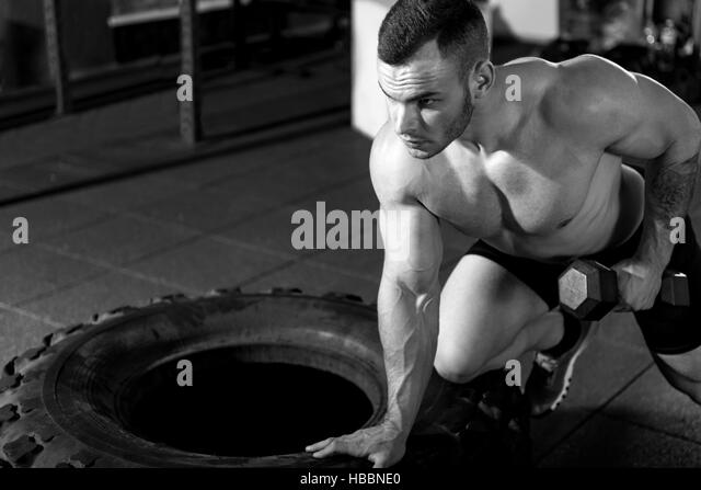 Athletic muscular man having weightlifting workout - Stock Image