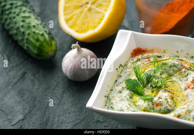 Tzatziki  on the stone table with cucumber , lemon and seasoning horizontal - Stock Image