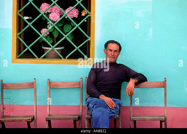 A fisherman sitting at the waterfront on the Italian island of Giglio. Stock Photo