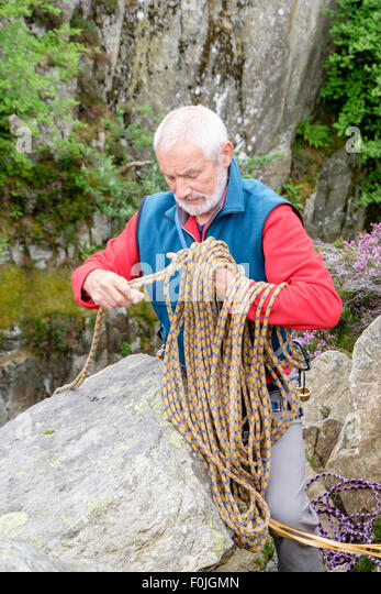 Experienced male rock climber unwrapping a climbing rope at top of a climb. North Wales, UK, Britain - Stock Image
