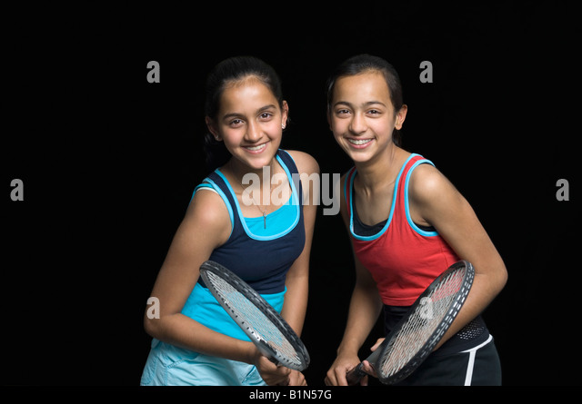 Portrait of a teenage girl smiling with her sister and holding badminton rackets - Stock Image