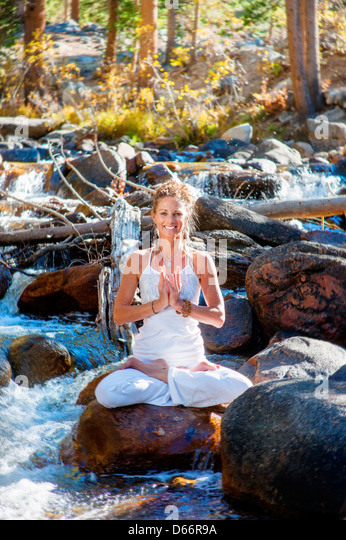 Smiling woman sitting in meditative lotus pose in a river - Stock Image