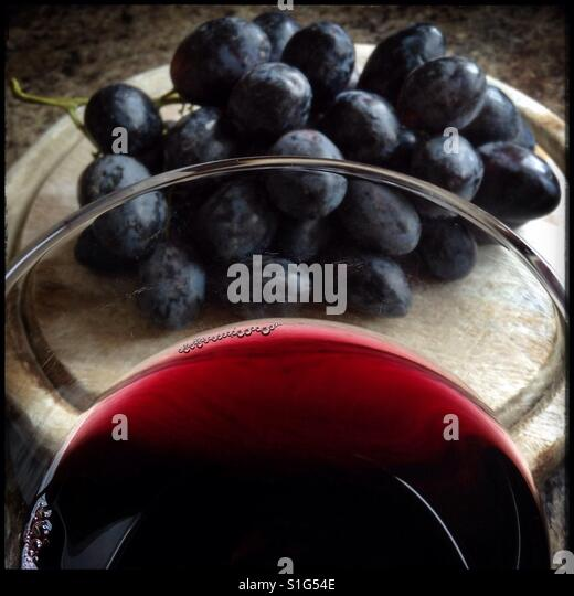A glass of red wine with some 'Autumn Royal' table [eating] grapes on a wooden board. - Stock-Bilder
