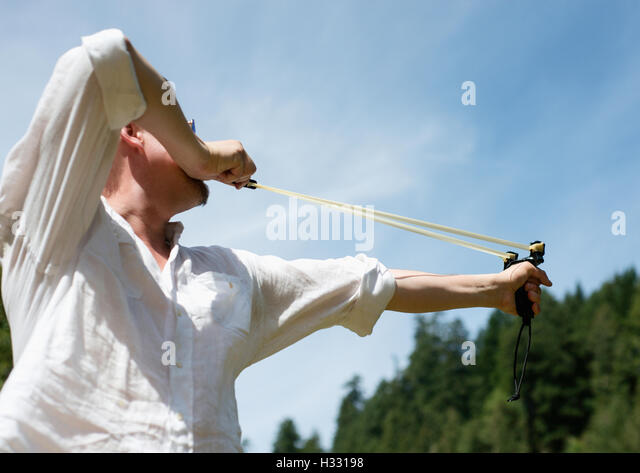 A man shooting a sling shot - Stock Image