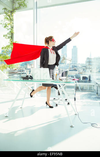 Businesswoman preparing to fly in cape and mask in office - Stock Image