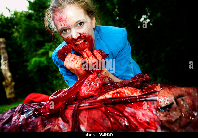 A woman dressed as a zombie eats a dead man - Stock Image