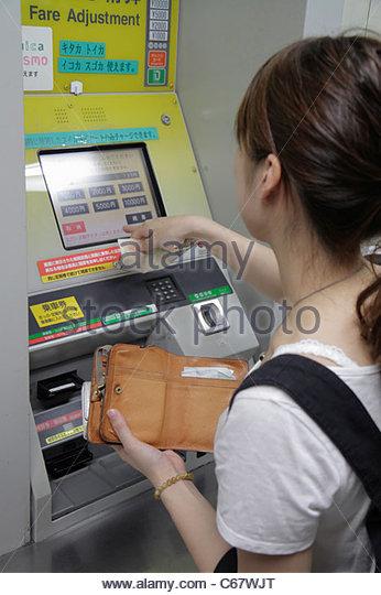Tokyo Japan Ikebukuro JR Ikebukuro Station Asian woman ticket vending machine Suica Pasmo card kanji hiragana characters - Stock Image