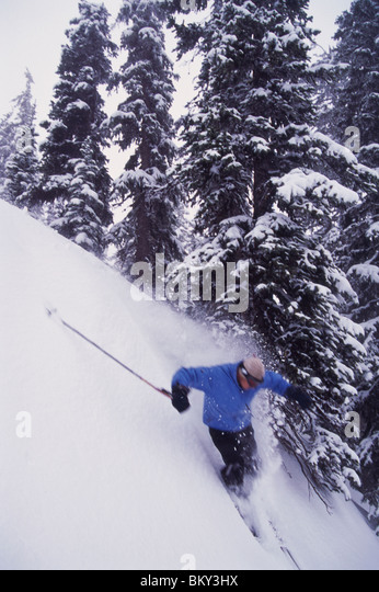 Man skiing a side country slope in Montana. - Stock Image