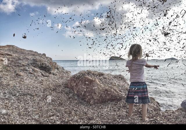 Girl throwing seaweed - Stock Image