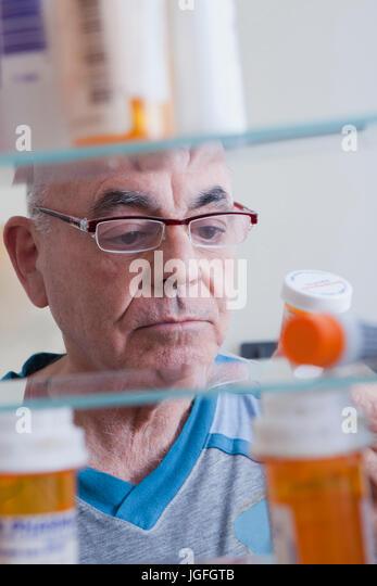 Hispanic man examining pill bottle from medicine cabinet - Stock Image