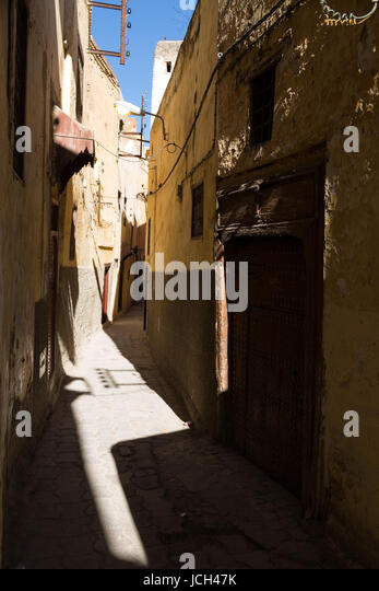 Harsh sun and shadows fall in a narrow alleyway between traditional houses in Meknes, Morocco - Stock Image