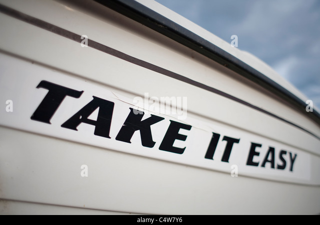 Sign on boat saying Take it Easy - Stock Image