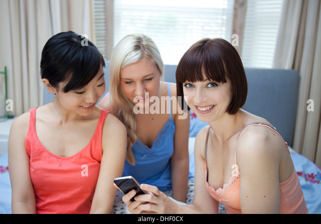 Group of young females on bed looking at mobile phone - Stock Image