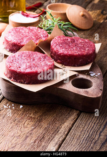 Organic raw ground beef, round patties for making homemade burger on wooden cutting board - Stock Image