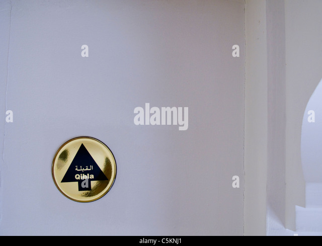 A Qibla, a brass plaque with arrow showing direction to Mecca to help Muslims to pray, set into ceiling of a hotel - Stock Image