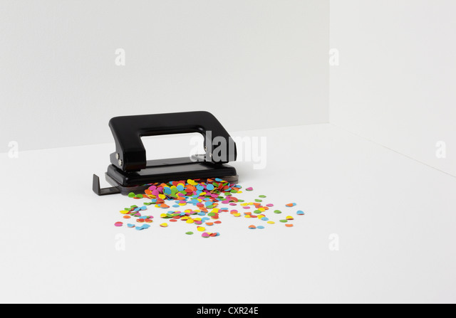 Hole puncher with multi coloured paper - Stock Image