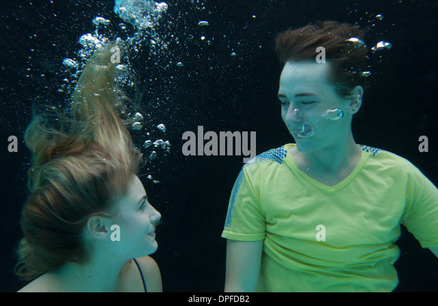 Young couple fully clothed floating underwater - Stock Image