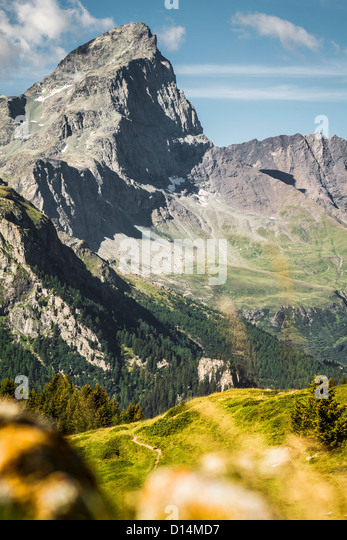 Rocky mountains over grassy landscape - Stock Image