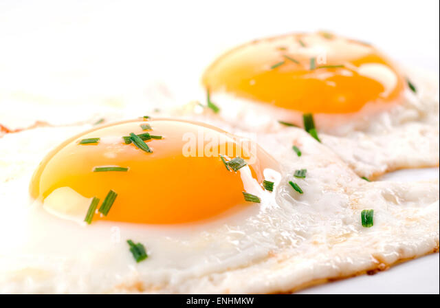 Two fried eggs with chive on top. - Stock Image