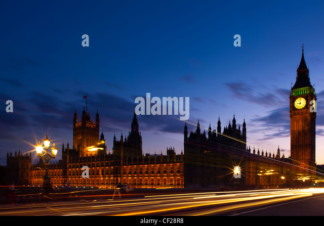 Light trails from traffic passing over Westminster Bridge with Big Ben and the Houses of Parliament in the background. - Stock Image