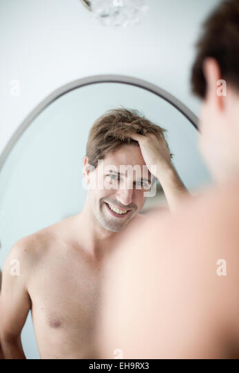 Man with hands in hair looking at self in mirror with look of amusement - Stock Image