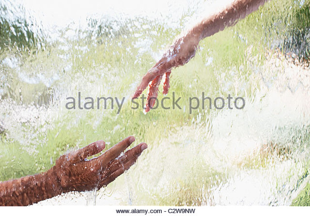 Two hands reaching out behind glass - Stock-Bilder