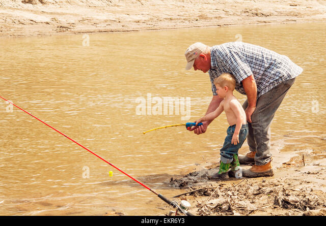 Grandfather teaching grandson to fish with toy rod and reel - Stock Image