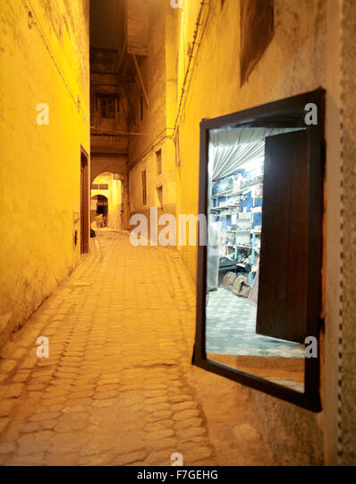 A mirror reflects a merchants store. In an alleyway in the Fes al Bali medina. Fes, Morocco, North Africa. - Stock Image