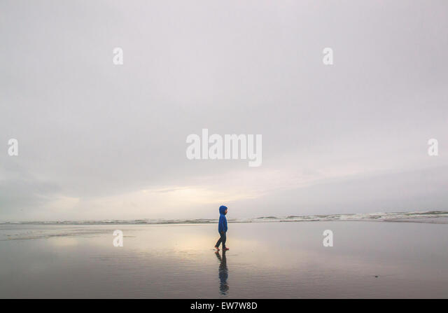 Boy walking on an empty beach - Stock Image