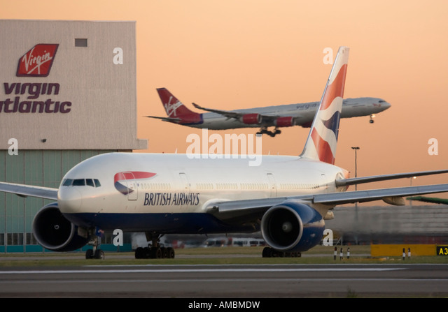 British Airways Boeing 777 taxiing for departure while Virgin Atlantic Airbus A340 landing in the background Heathrow - Stock Image