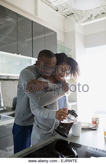 Smiling couple hugging and pouring morning coffee - Stock Image