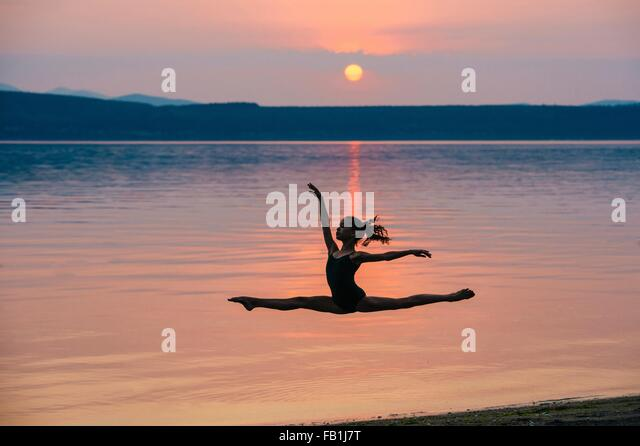 Side view of girl by ocean at sunset leaping in mid air, arms raised doing the splits - Stock Image
