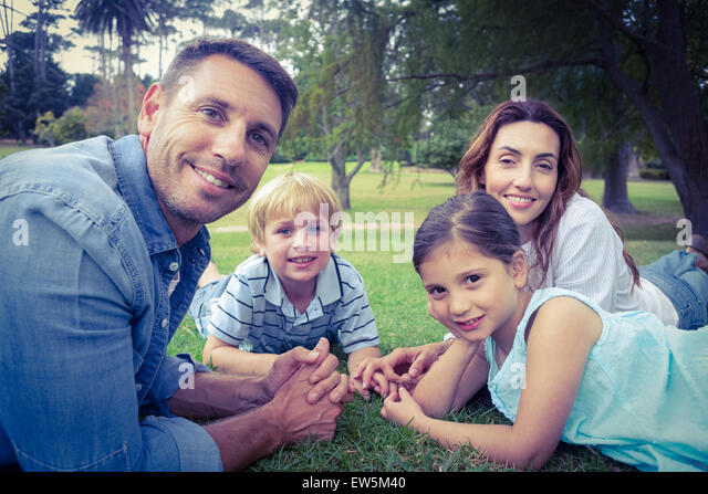 Happy family in the park lying down together - Stock Image