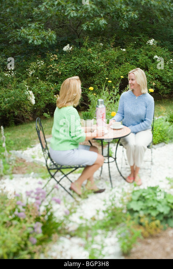 Mature woman and a mid adult woman sitting together in a tea party - Stock-Bilder