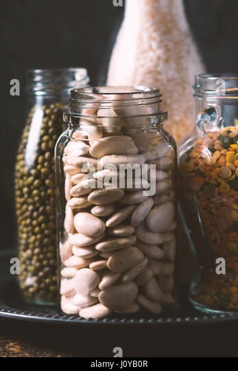 Rice, lentils, white beans in bottles side view vertical - Stock Image
