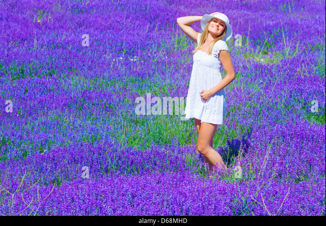 Pretty girl tanning in lavender glade, enjoying bright sun light and purple flowers landscape, having fun outdoors - Stock Image