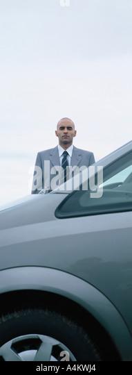 Man standing behind car - Stock Image