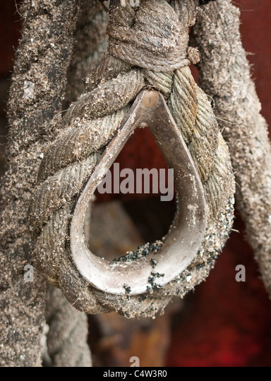 A rope hook attached to a tractor used for pulling fishing boats up and down a beach - Stock Image