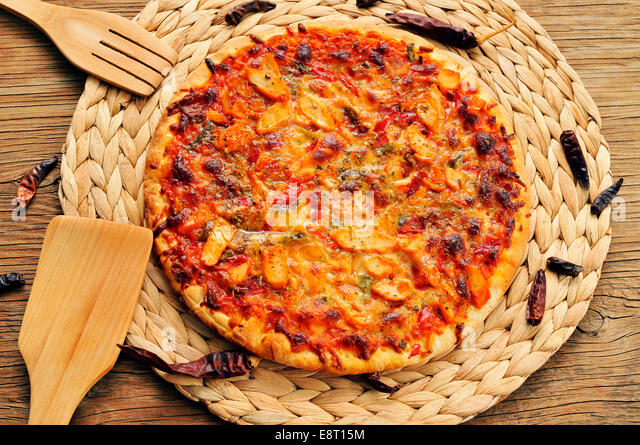 a pizza with chicken, red pepper and green pepper, served on a wooden background - Stock Image