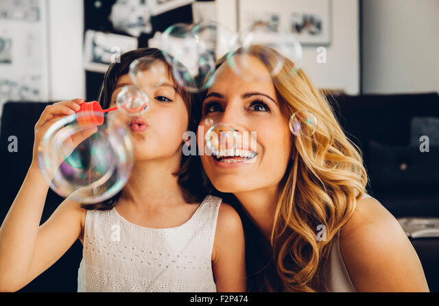 Happy mother with daughter at home blowing soap bubbles - Stock Image