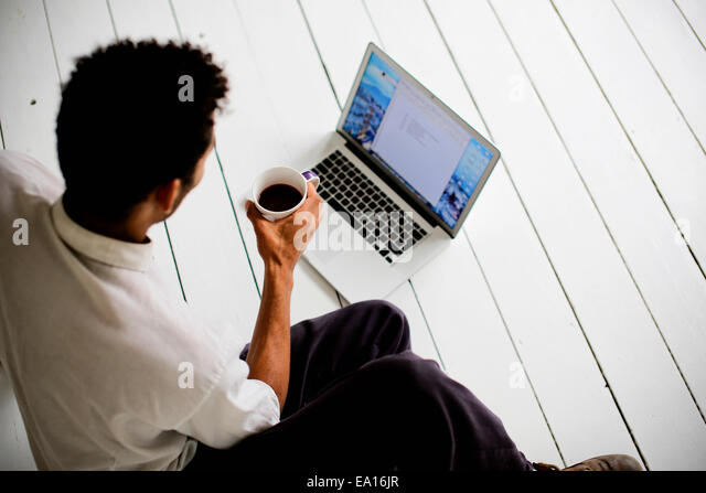 Graphic designer using laptop on floor - Stock-Bilder